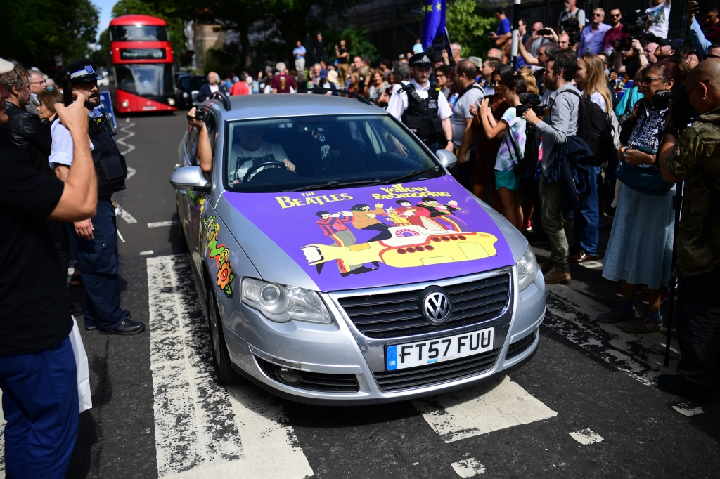 A car with Beatles 'Yellow Submarine' decals drives over the famous zebra crossing after Beatles impersonators recreated the iconic 'Abbey Road' photograph made 50 years ago today.