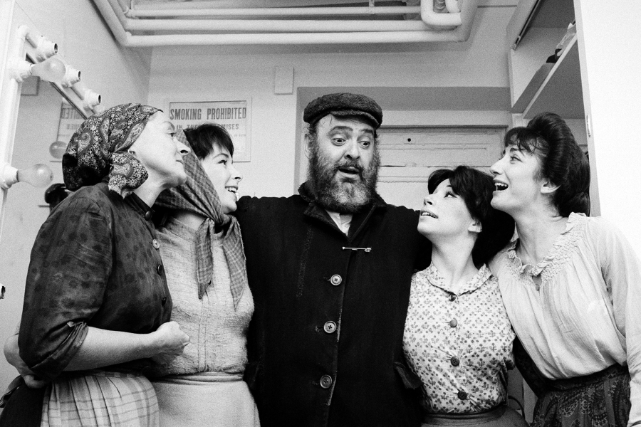 "Actor Zero Mostel, center, who portrays Tevye in the musical ""Fiddler on the Roof,"" poses backstage with cast members after the play's opening performance at the Imperial Theatre in New York City on Sept. 22, 1964.  Maria Karnilova, who plays Tevye's wife, Golde, is at far left.  Playing Tevye's daughters, from left, are, Tanya Everett, as Chava; Julia Migenes, as Hodel; and Joanna Merlin, as Tzeitel.  (AP Photo)"