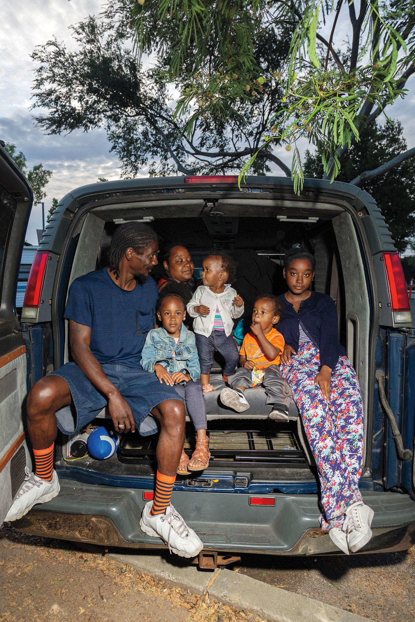 Ray Adkins, far left, and Christina Wade, second from the left, and their children, Eleisha Wade, 4, Avia Wade, 1, Adriel Adkins, 2, and Auneste Caldwell, 16, sit in their van where they used to sleep while staying in the LifeMove Safe and Supportive Parking lot in San Jose. The family stayed on the safe lot for two weeks before finding housing. Photographs by Erin Brethauer