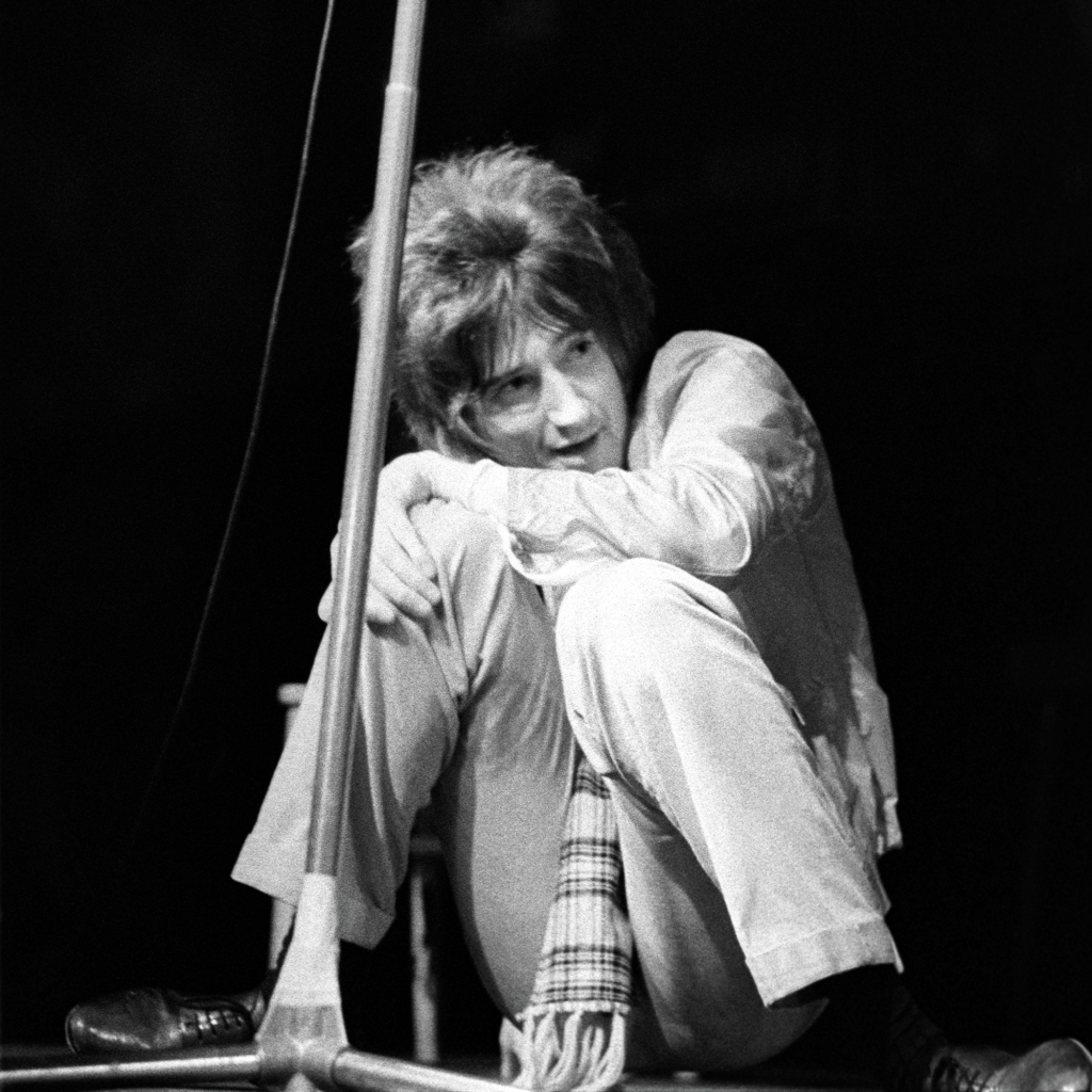 """Rod Stewart fronting the Jeff Beck Group at the Fillmore West in San Francisco in 1968. """"For a concert photographer, it's important the performers do more than play music,"""" Wolman says. """"The more they 'perform'…the better the pictures.""""He notes Stewart's striking pose: """"He is doing something distinctively non-musical which I find hilarious. What does squatting on the stage have to do with his role as a singer? The bands of San Francisco wouldn't be caught dead wearing a scarf like that or leather shoes like that. Most of the Bay Area bands were hippies with leather fringe and the like."""""""