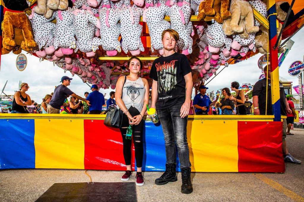 Chloe Tuttle and Alex Mulder stand for a portrait in front of a game at the Iowa State Fair in Des Moines, Iowa on August 10, 2019 before a Slipknot concert.