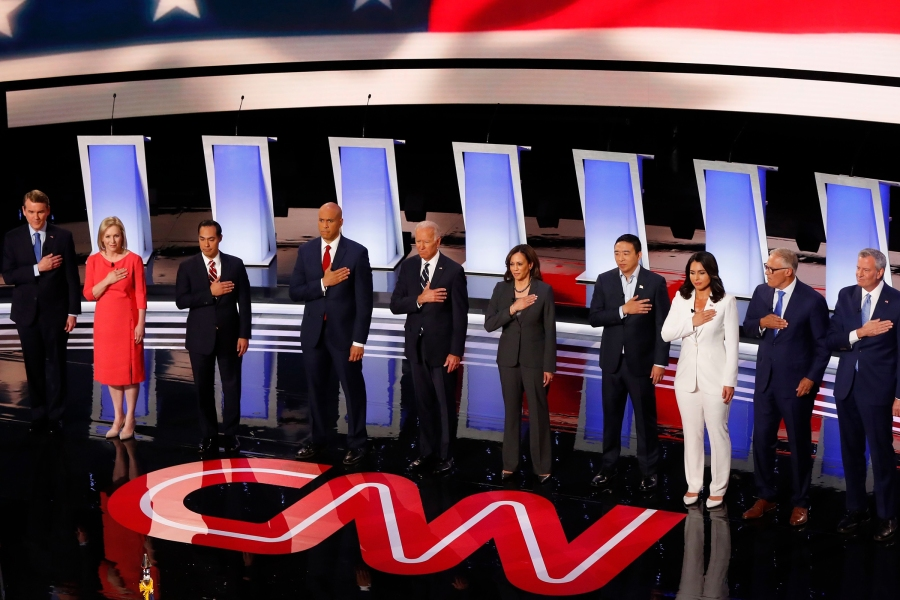From left, Sen. Michael Bennet, D-Colo., Sen. Kirsten Gillibrand, D-N.Y., former Housing and Urban Development Secretary Julian Castro, Sen. Cory Booker, D-N.J., former Vice President Joe Biden, Sen. Kamala Harris, D-Calif., Andrew Yang, Rep. Tulsi Gabbard, D-Hawaii, Washington Gov. Jay Inslee and New York City Mayor Bill de Blasio stand for the National Anthem as they are introduced before the second of two Democratic presidential primary debates hosted by CNN, in the Fox Theatre in DetroitElection 2020 Debate, Detroit, USA - 31 Jul 2019