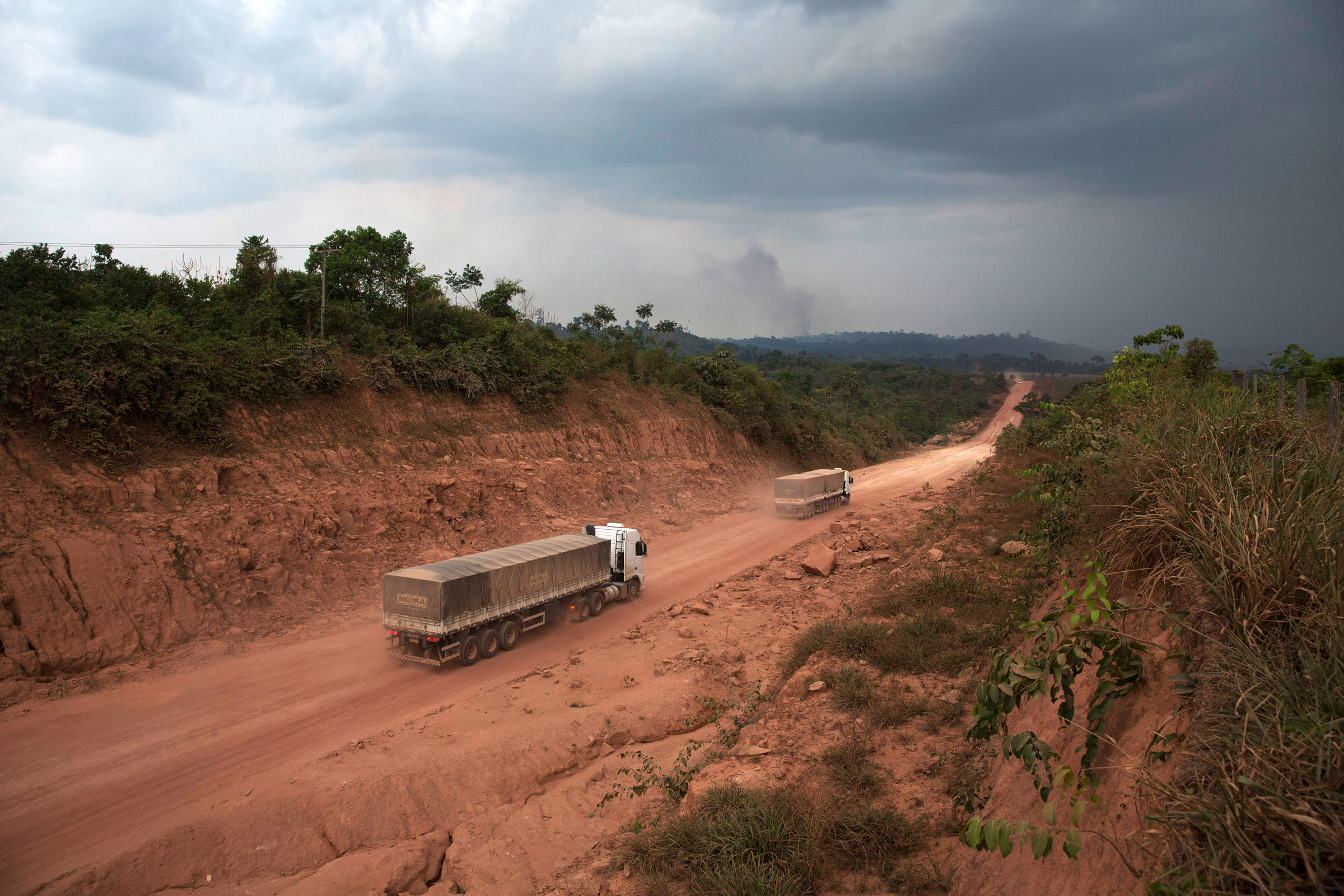 Trucks make their way down an unpaved stretch of BR-163 close to Novo Progresso, Brazil, Sept. 25, 2014. Long stretches of the road through the Amazon are still unpaved, with mud and potholes among the issues facing drivers. ?This place is like a little bit of hell,? said Eduardo Pimentel, a truck driver. (Lalo de Almeida/The New York Times)