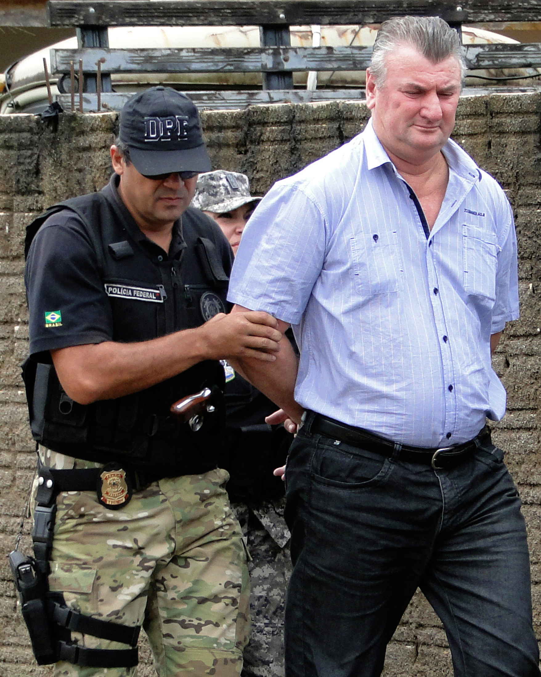 Ezequiel Antonio Castanha (R), who is accused of illegally destroying tens of thousands of square kilometres of Amazon forest, walks with a federal police officer in Novo Progresso in the northern state of Para February 22, 2015. Castanha was arrested in Para on Monday following a six-month joint operation involving federal police, the public ministry and Brazil's environmental protection agency, the Institute of Environment and Renewable Natural Resources (IBAMA), said. The environmental damage has been estimated to be in the hundreds of millions of dollars. Once the public lands were cleared of forest, prosecutors say Castanha and the gang he worked with would illegally sell land plots to ranchers for as much as $6.95 million. Picture taken February 22, 2015. REUTERS/Folha do Progresso/Juliano Simionato (BRAZIL - Tags: ENVIRONMENT CRIME LAW TPX IMAGES OF THE DAY) - GM1EB2O1TC501