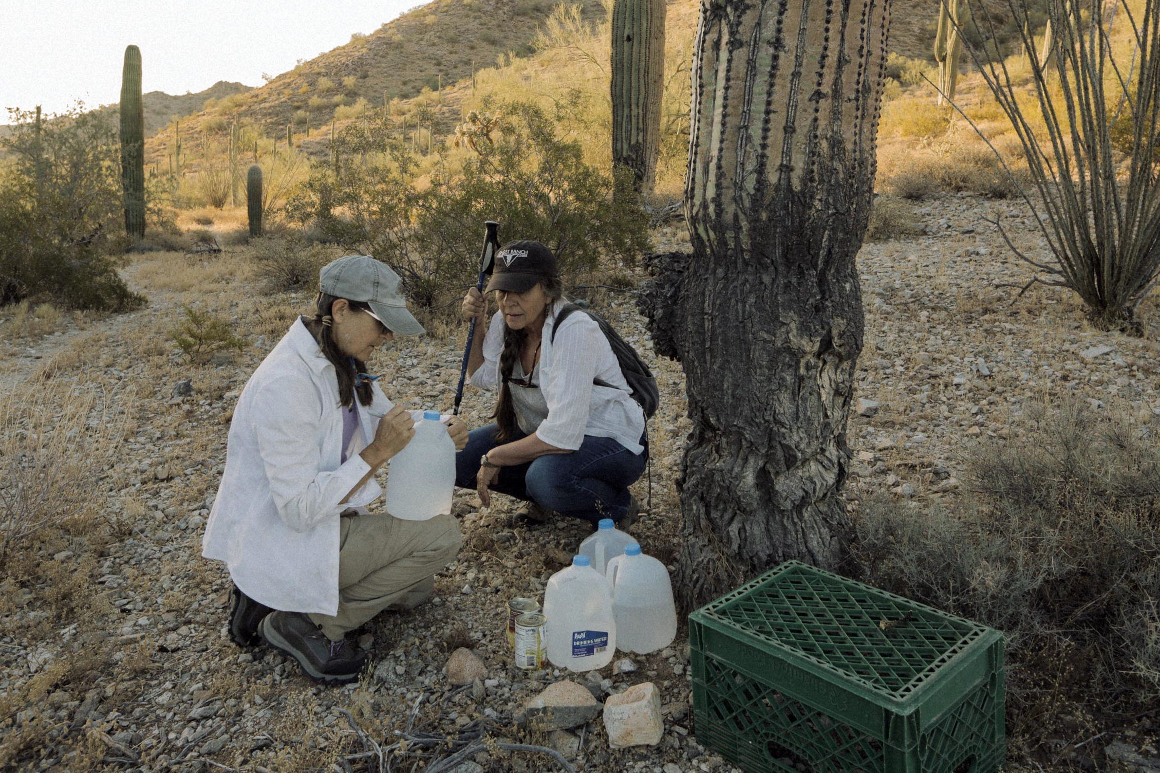 3005: Cheryl Opalski, an Ajo resident and volunteer with the Samaritans, makes a water drop with a new member near the boundary line of Cabeza Prieta National Wildlife Refuge, AZ. June 2019. Photo by Jason Motlagh.