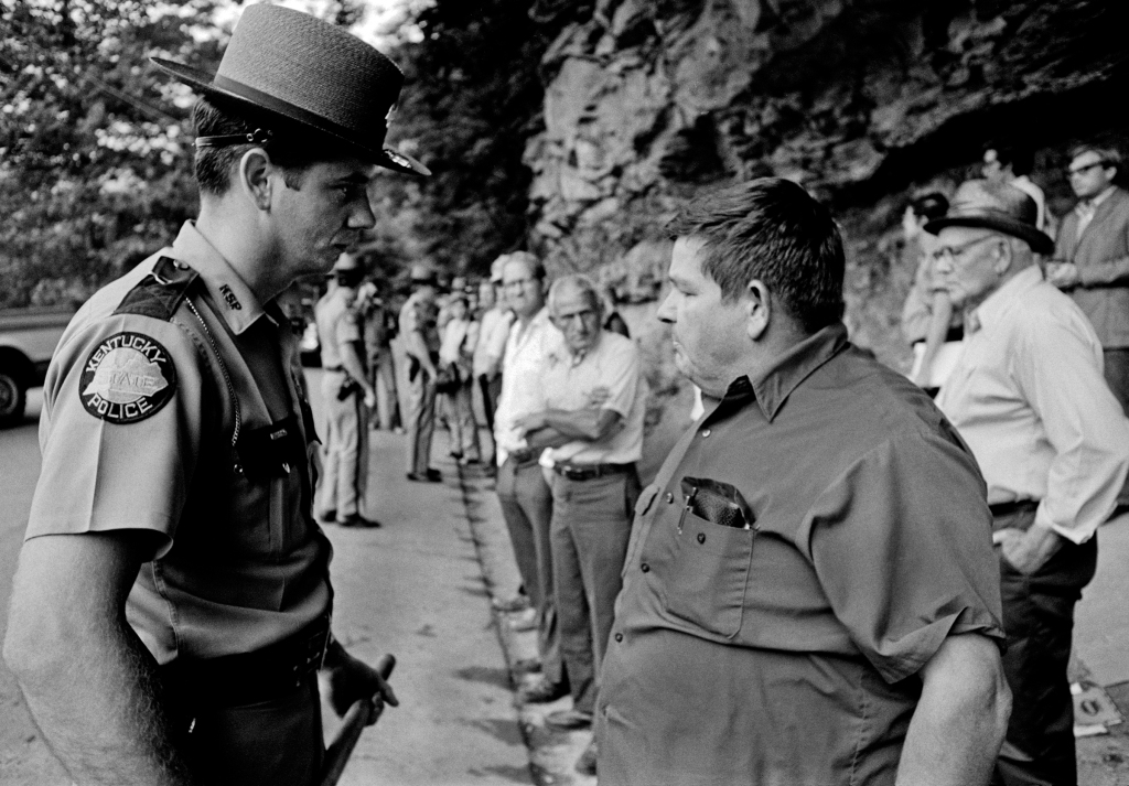 "1974, August. Harlan County USA: Outside the Highsplint mine in Harlan, County, KY United Mineworkers of America (UMWA) strikers and supporters confront state police and striker breakers. Strike struck the Highsplint mine for union recognition and in support of the contract strike at Brookside mine a few miles down the road. Before the union won the right to an election one miner was shot dead by company ""security"" while having a beer with friends."