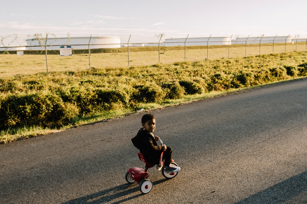 A young boy rides his tricycle on Burton Lane in St. James. The dead-end residential road is surrounded on three sides by heavy industry.