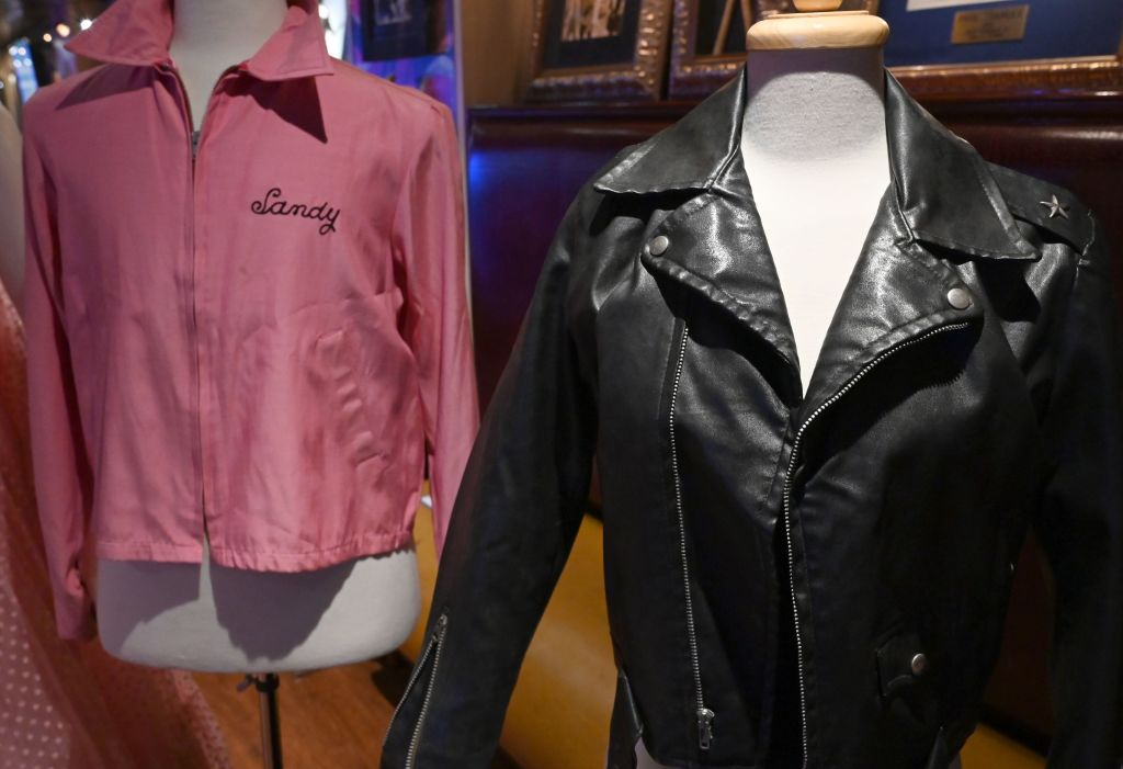 "Olivia Newton-John's famous black leather jacket worn in the blockbuster film ""Grease"" and her Grease ""Pink Ladies"" jacket worn in the film are shown during a Julien's Auctions press preview at Hard Rock Cafe in New York on October 16, 2019. - Over 500 of the most iconic film and television worn costumes, ensembles, gowns, personal items and accessories owned and used by the four-time Grammy award-winning singer/Hollywood film star and the proceeeds will benefit the Olivia Newton-John Cancer Wellness & Research Centre. (Photo by TIMOTHY A. CLARY / AFP) (Photo by TIMOTHY A. CLARY/AFP via Getty Images)"