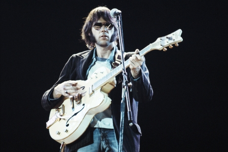 Canadian musician Neil Young of Crosby, Stills, Nash And Young performs on stage at Wembley Stadium, London on September 14th 1974. (Photo by Michael Putland/Getty Images)