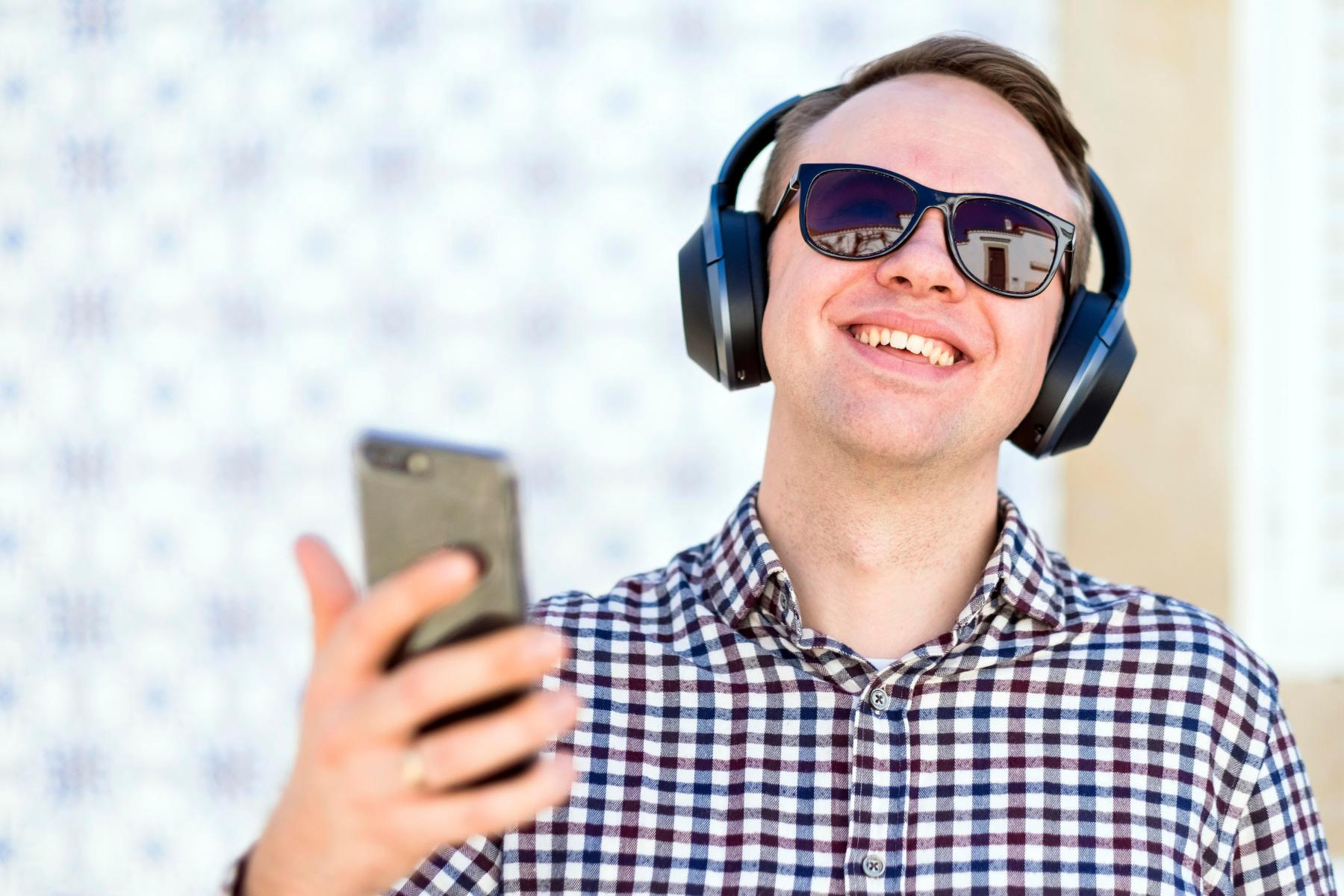 MODEL RELEASED Young man with modern, wireless bluetooth-headphones enjoying the music from his smartphoneVARIOUS