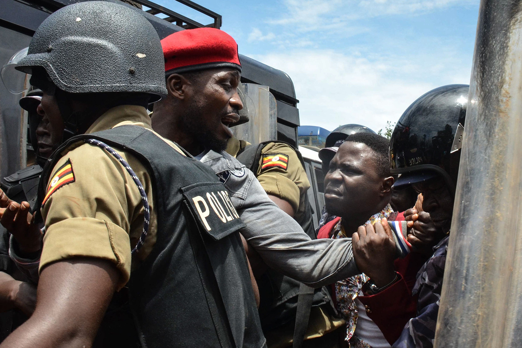 "Ugandan musician turned politician Robert Kyagulanyi, commonly known as Bobi Wine, is arrested by police on his way to a press conference held to announce the cancelation of his show at Busabala, Uganda, on April 22, 2019. - Ugandan police detained pop star-turned-MP Bobi Wine on April 22, 2019 after shutting down one of his concerts and firing tear gas at his fans, the singer's wife and supporters said. ""He has been arrested in Busabala, where he was to address the media on the cancellation of his concert by the police,"" Wine's wife Barbie Itungo Kyagulanyi told AFP, referring to a suburb in southern Kampala. (Photo by Badru KATUMBA / AFP) (Photo credit should read BADRU KATUMBA/AFP via Getty Images)"