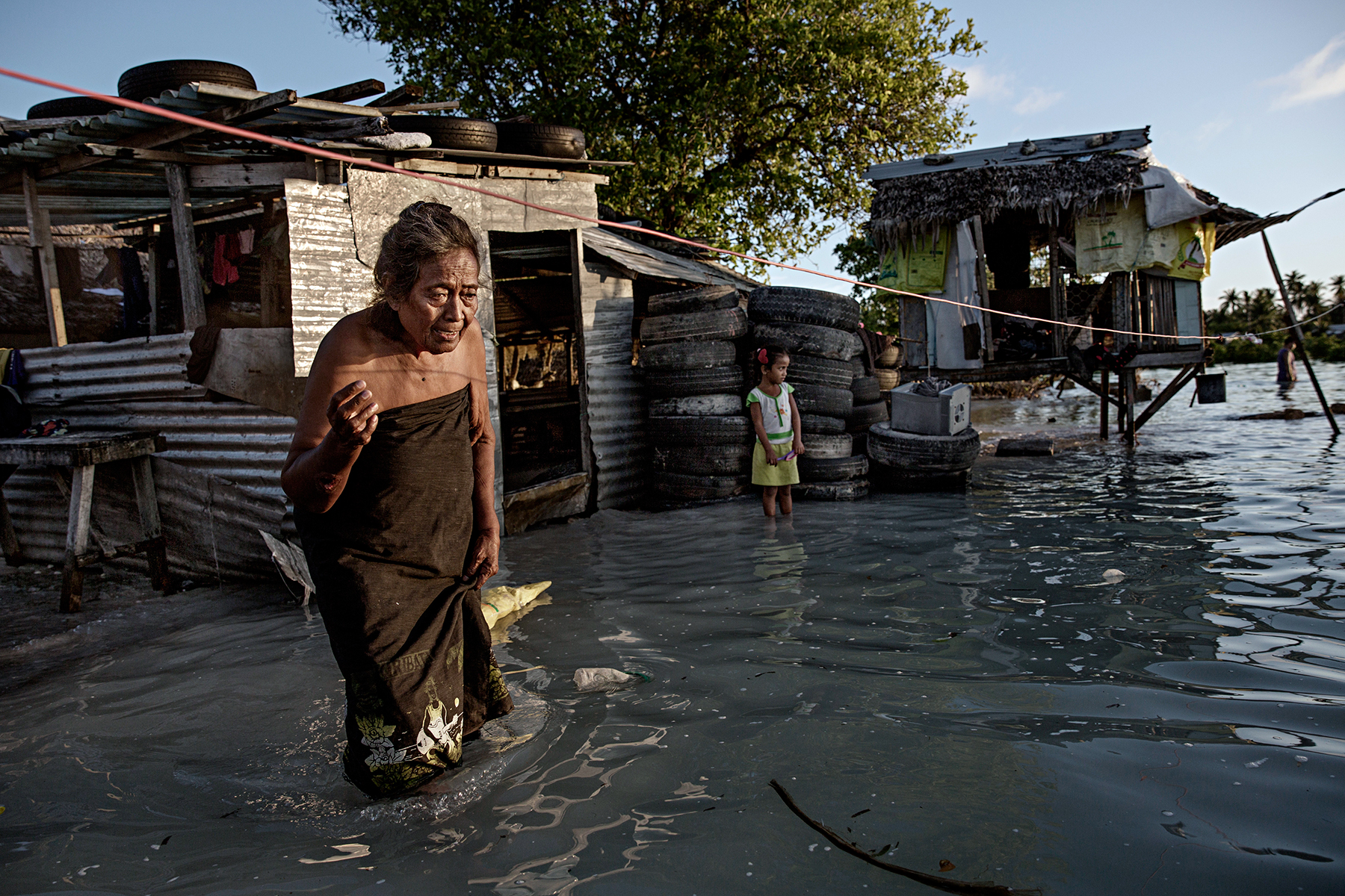 EITA, TARAWA, KIRIBATI - 2015/09/30: An elderly woman wades through knee-high sea water that flooded her house and village. The people of Kiribati are under pressure to relocate due to sea level rise. Each year, the sea level rises by about half an inch. Though this may not sound like much, it is a big deal considering the islands are only a few feet above sea level, which puts them at risk of flooding and sea swells. It is well agreeable that the people of Kiribati account for little to nothing in terms of green house emissions but are forced to face the direct consequences of global warming. And with an average age of 22, Kiribati's future generations are at risk of potentially lethal sea level rise. (Photo by Jonas Gratzer/LightRocket via Getty Images)