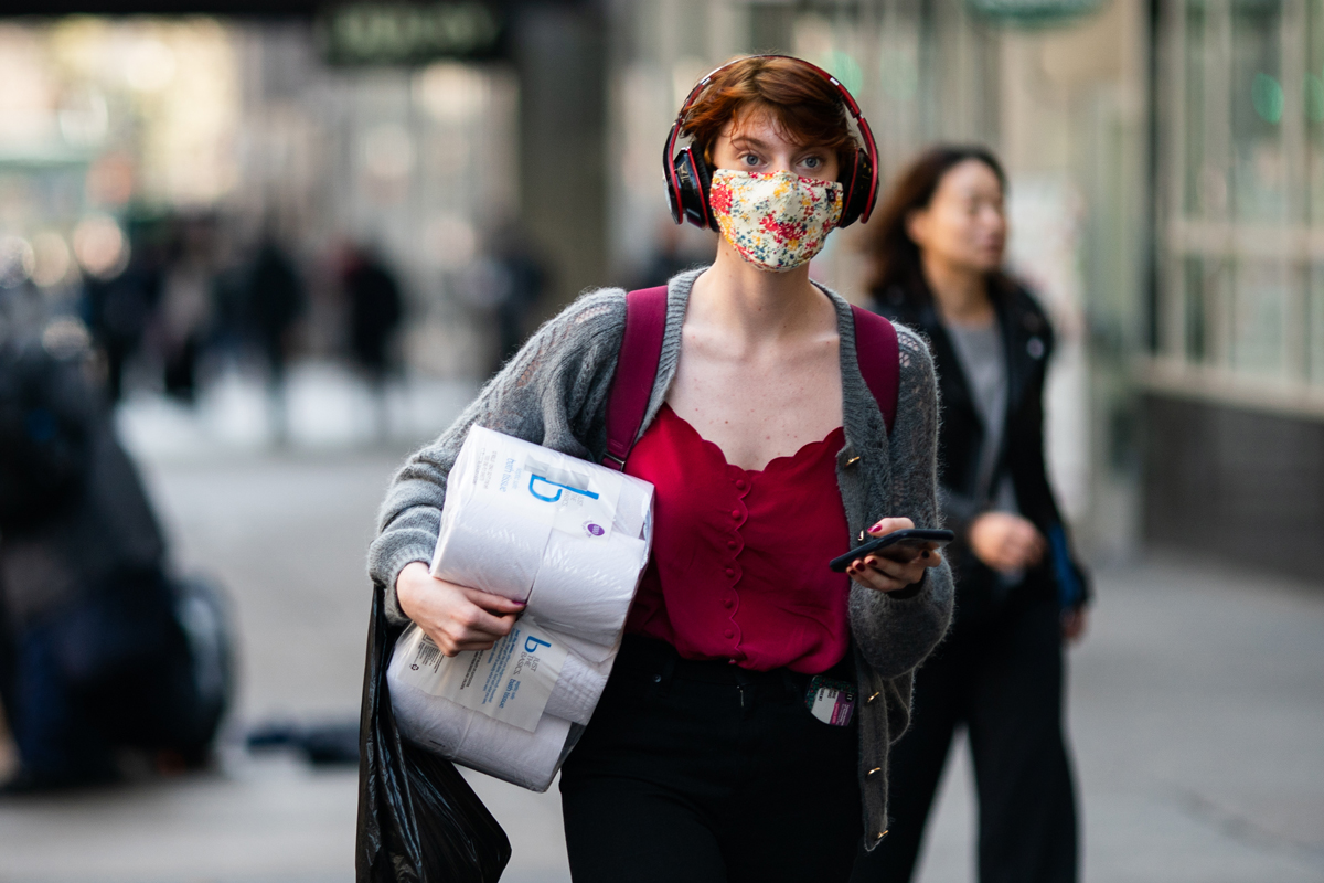 A woman wearing a protective mask carries a toilet paper package on the street on March 13, 2020 in New York City.