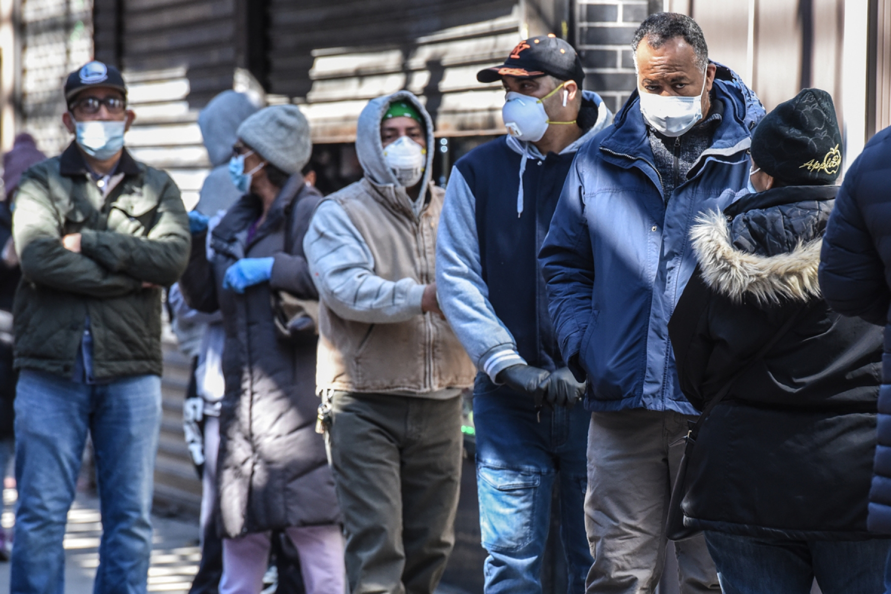 People stand in line while wearing face masks in the Elmhurst neighborhood on April 1, 2020 in New York City.