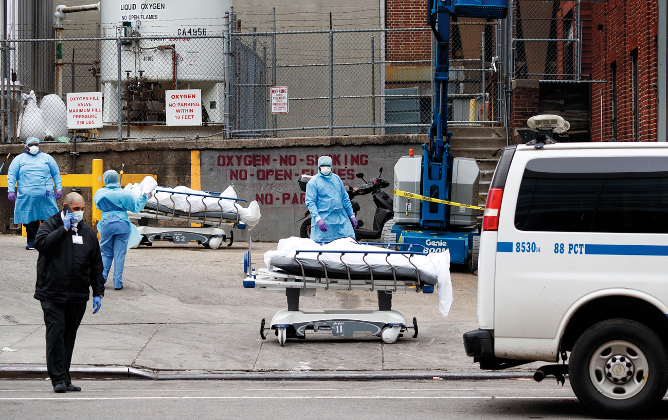 A medical professionals stand with bodies on hospital gurneys as they are moved to be temporarily stored in a mobile morgue, put in place due to lack of space at the hospital, outside of the Brooklyn Hospital Center in Brooklyn, New York, USA, on 30 March 2020. New York City is still the epicenter of the coronavirus outbreak in the United States and as of Monday there were reportedly 1,218 people who have died as a result of complications from COVID-19.New York Coronavirus Cases, Brooklyn, USA - 30 Mar 2020