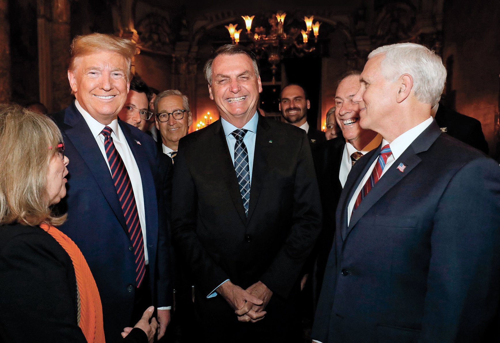 In this March 7, 2020 photo provided by Brazil's presidential press office, Brazil's President Jair Bolsonaro, center, stands with President Donald Trump, second from left, Vice President Mike Pence, right, and Brazil's Communications Director Fabio Wajngarten, behind Trump partially covered, during a dinner in Florida. Wajngarten tested positive for the new coronavirus, just days after the trip, according to Bolsonaro's communications office onVirus Outbreak Brazil, Florida, United States - 07 Mar 2020