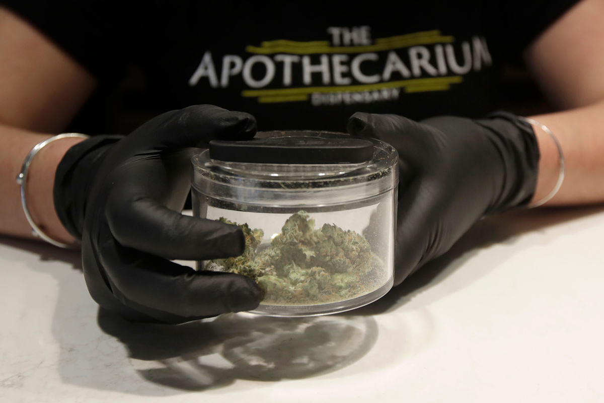 "Cali Manzello, general manager at The Apothecarium cannabis dispensary, wears gloves when holding a marijuana sample for smelling while posing for photos at the store in San Francisco, . As about 7 million people in the San Francisco Bay Area are under shelter-in-place orders, only allowed to leave their homes for crucial needs in an attempt to slow virus spread, marijuana stores remain open and are being considered ""essential servicesVirus Outbreak California Marijuana, San Francisco, United States - 18 Mar 2020"