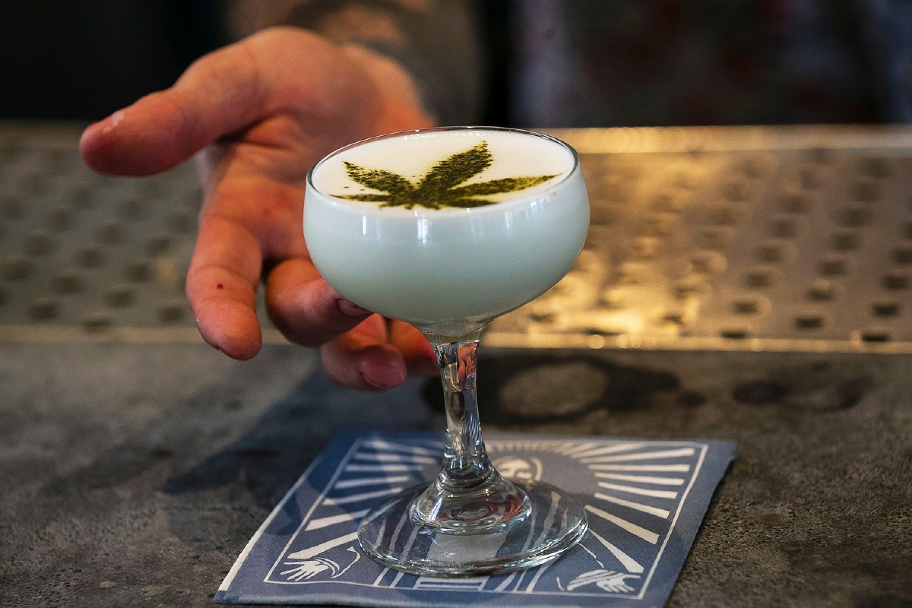 Maxwell Reis, beverage director serves a drink containing Cannabidol CBD extract with a marijuana leaf motif at the Gracias Madre restaurant in West Hollywood, California.