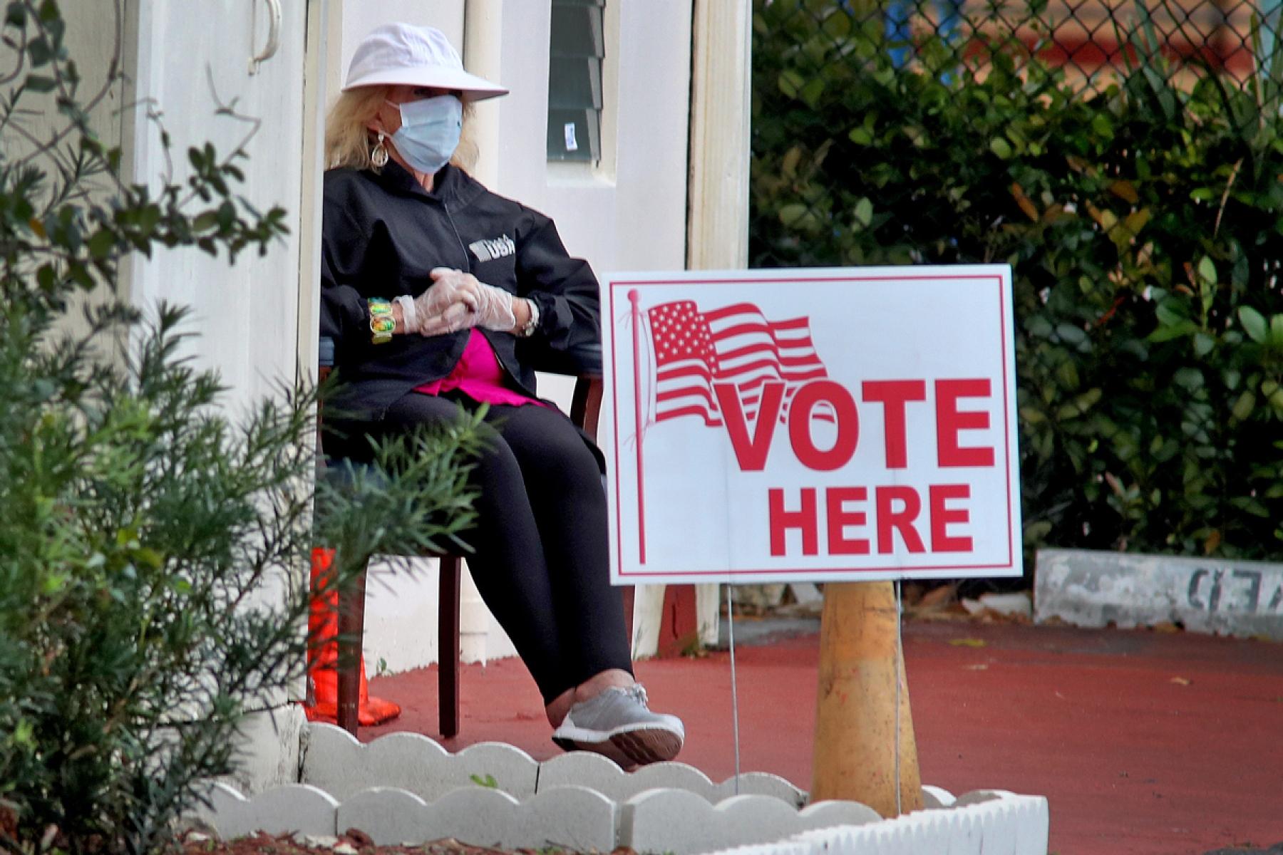 A poll worker at the First Baptist Church voting site in Hollywood, Florida, wears a protective mask and gloves on Tuesday, March 17, 2020. Voting in Florida's presidential primary is proceeding despite the novel coronavirus.