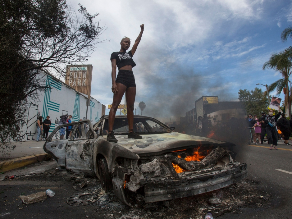 Protester stands on a burning police vehicle during a protest over the death of George Floyd, a handcuffed black man in police custody in Minneapolis, in Los Angeles CA on May 30th 2020