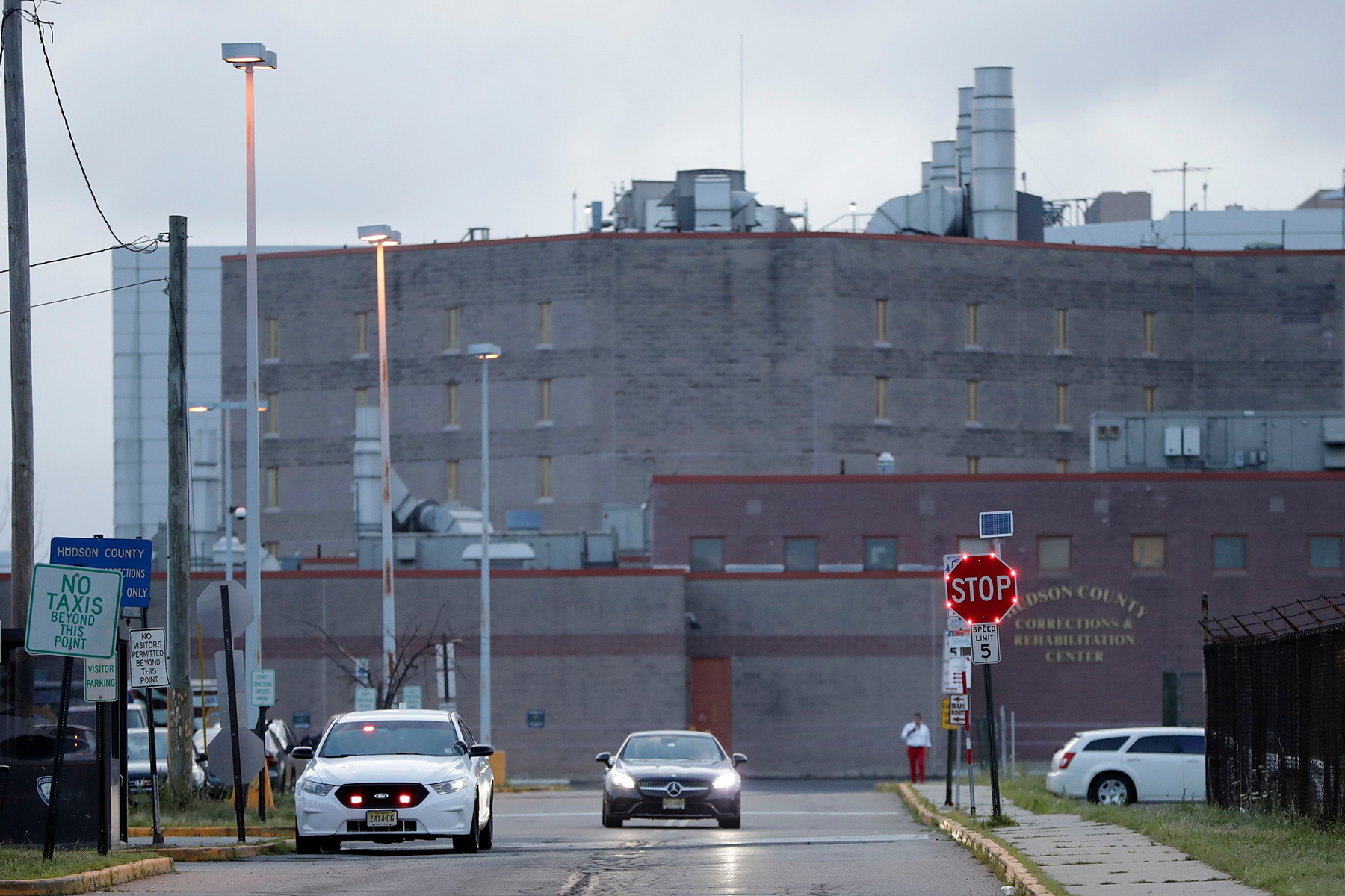 An official's vehicle, left, is parked near the exit to the Hudson County Correctional Facility, in Kearny, N.J. A judge on Tuesday ordered the immediate release of Pablo Villavicencio, an Ecuadorean immigrant who is being held at the facility for deportation after he delivered pizza to a Brooklyn Army installation. U.S. District Judge Paul Crotty said Villavicencio can remain in the United States while he exhausts his right to try to gain legal status. Villavicencio applied to stay in the U.S. after he married a U.S. citizen, with whom he has two young girlsImmigration Pizza Delivery, Kearny, USA - 24 Jul 2018