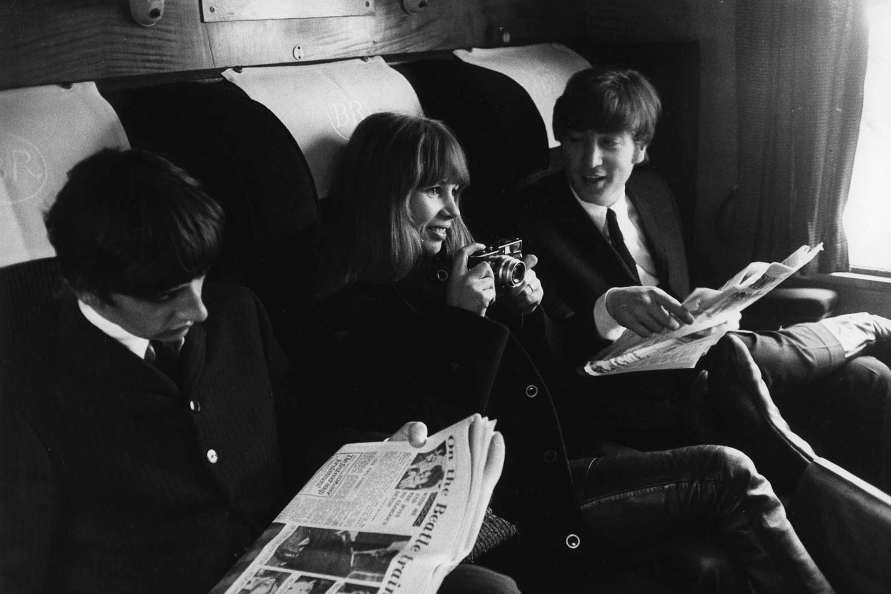 """UNSPECIFIED - CIRCA 1960:  Photo of John LENNON and Astrid KIRCHHERR and BEATLES; L-R: Ringo Starr, Astrid Kirchherr (holding camera) & John Lennon - sitting on train during the filming of """"A Hard Day's Night""""  (Photo by Max Scheler - K & K/Redferns)"""