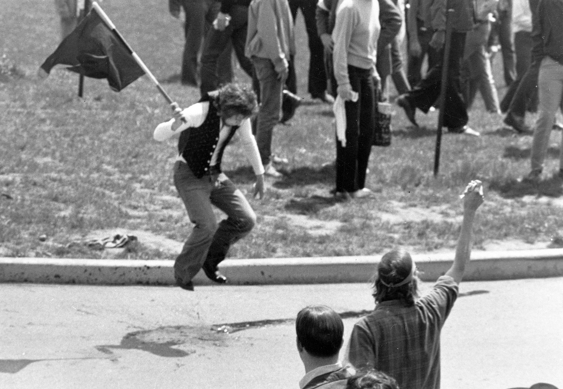 (Original Caption) Kent, Ohio: Irate Protester. A flag-waving antiwar demonstrator on Kent State University campus May 4, jumps up and down on the spilled blood of one of the students shot down by Ohio National Guardsmen here during a demonstration protesting the United States' invasion of Cambodia. The photo was released May 5 by the Kent State News Bureau.
