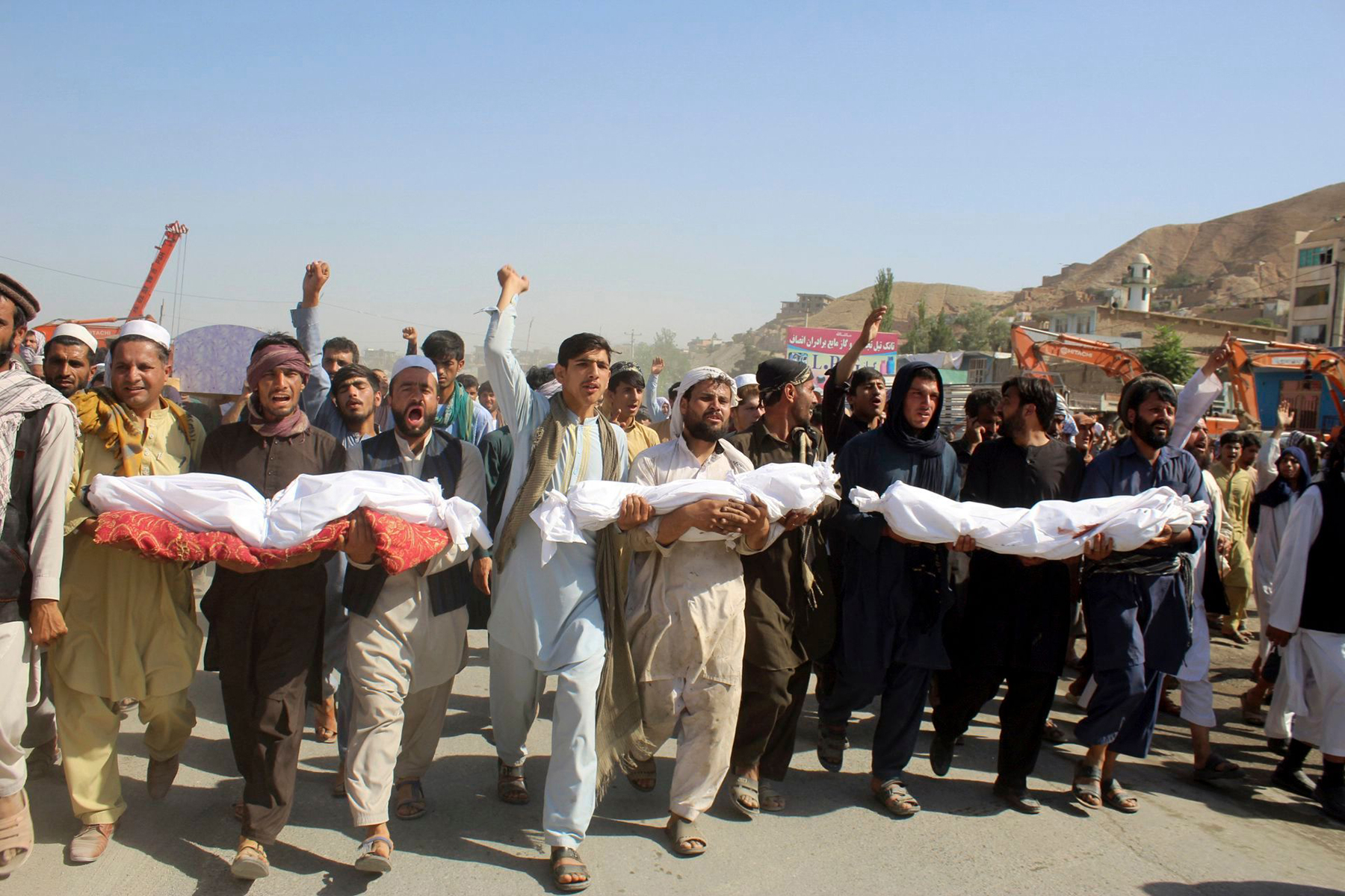 Residents carry bodies killed in an airstrike during a protest in Baghlan province, northern Afghanistan, Tuesday, July 9, 2019. Even as an All-Afghan conference that brought Afghanistan's warring sides together was ending, the airstrike killed seven people, six of them children.