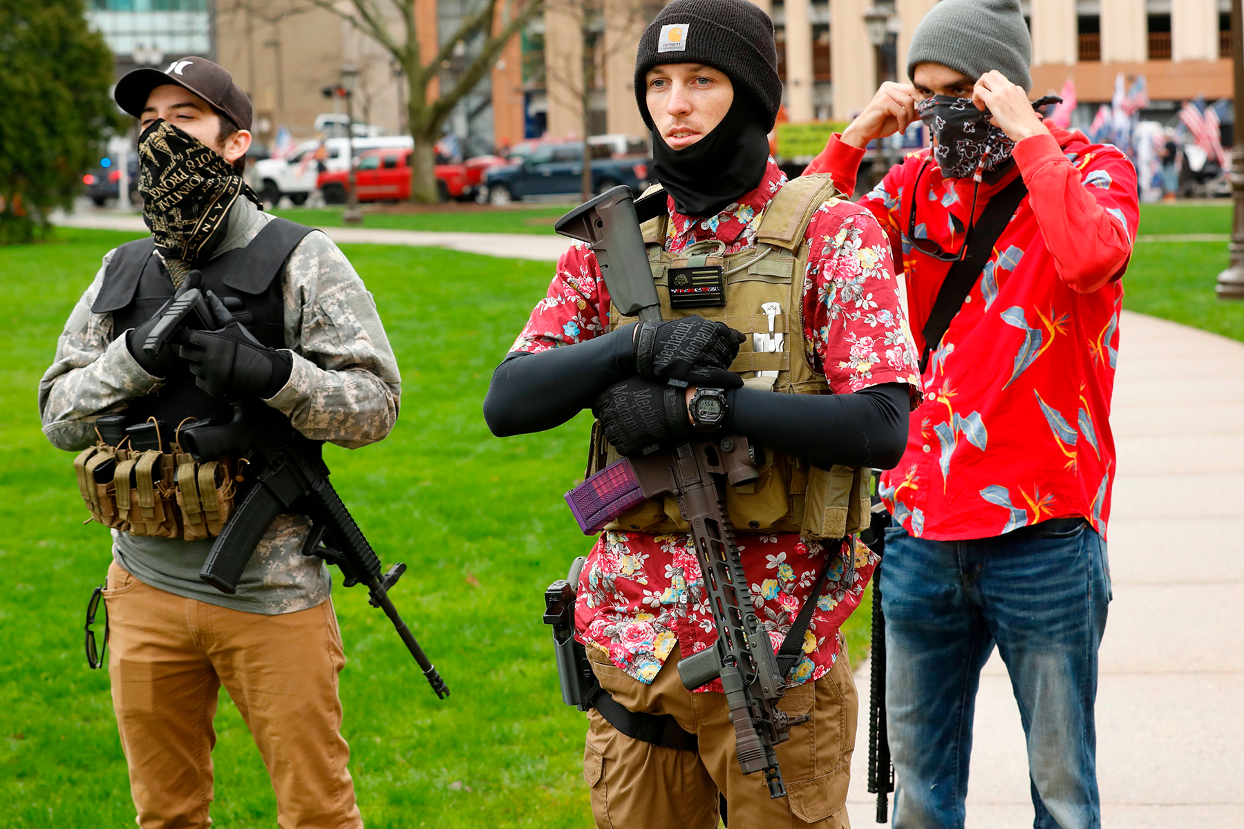 """Armed protesters provide security as demonstrators take part in an """"American Patriot Rally,"""" organized on April 30, 2020, by Michigan United for Liberty on the steps of the Michigan State Capitol in Lansing, demanding the reopening of businesses. - Michigan's stay-at-home order declared by Democratic Governor Gretchen Whitmer is set to expire after May 15. (Photo by JEFF KOWALSKY / AFP) (Photo by JEFF KOWALSKY/AFP via Getty Images)"""