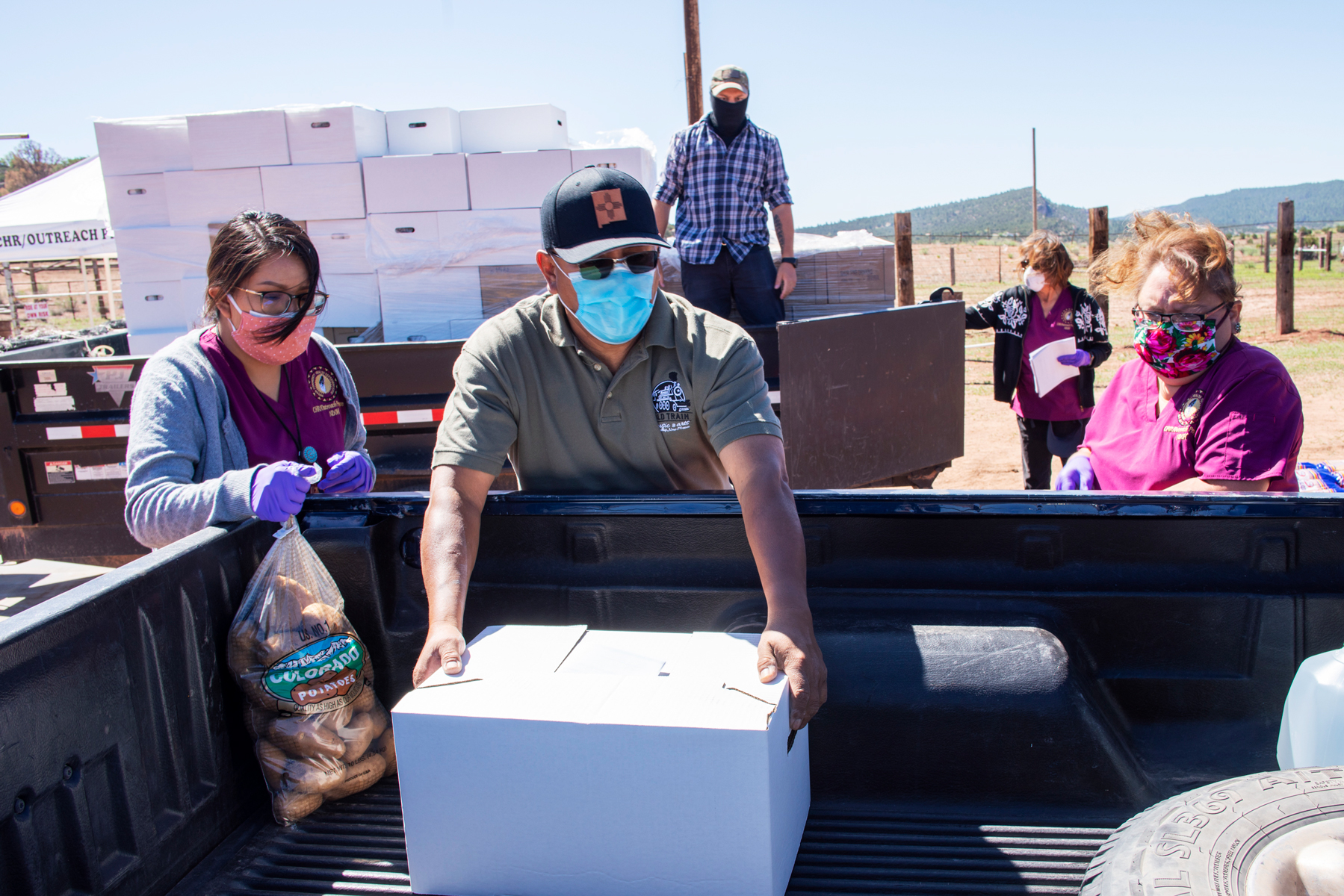 Sam Bryant of the Southwest Indian Foundation in Gallup loads a box of groceries into a pickup on the Navajo Reservation at Oak Springs, Arizona.