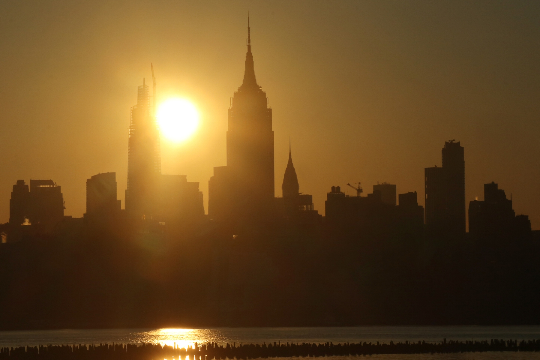 JERSEY CITY, NJ - JUNE 26: The sun rises behind the Chrysler Building, Empire State Building, and One Vanderbilt in New York City on June 26, 2020 as seen from Jersey City, NJ. (Photo by Gary Hershorn/Getty Images)