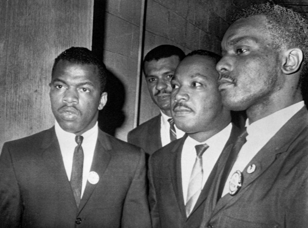 Reverend Martin Luther King Jr., (center) is escorted into a mass meeting at Fish University in Nashville. His colleagues are, left to right, John Lewis, national chairman of the Student Non-Violent Committee and Lester McKinnie, on of the leaders in the racial demonstrations in Nashville recently. King gave the main address to a packed crowd. (Photo by Bettmann Archive/Getty Images)