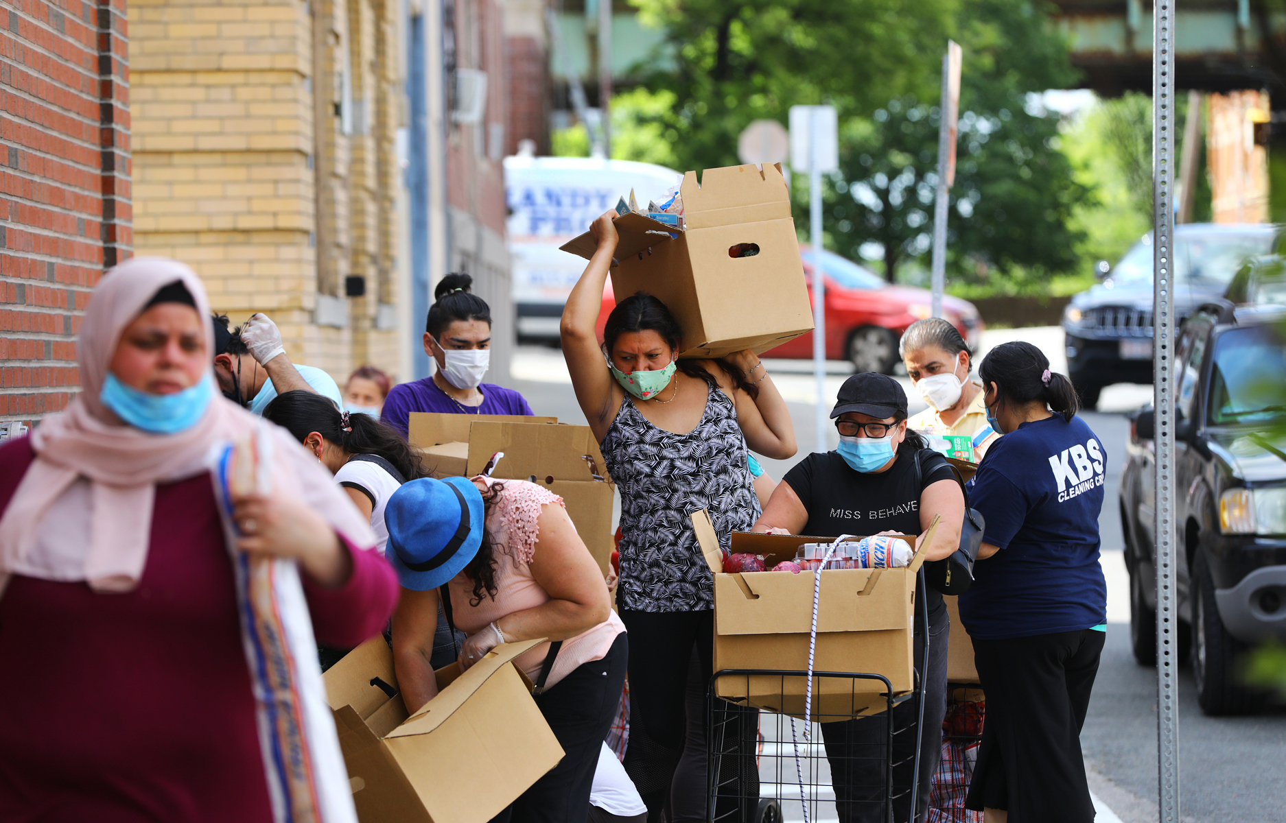 People get provisions from the food pantry line at the Chelsea Collaborative during the coronavirus pandemic in Chelsea, MA on June 4, 2020.
