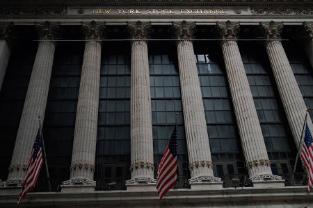 American flags are seen outside the New York Stock Exchange (NYSE) on July 20, 2020 at Wall Street in New York City. - Wall Street stocks were mixed early July, 20, 2020 as markets awaited congressional debate on another round of stimulus spending and major earnings releases later in the week. (Photo by Johannes EISELE / AFP) (Photo by JOHANNES EISELE/AFP via Getty Images)