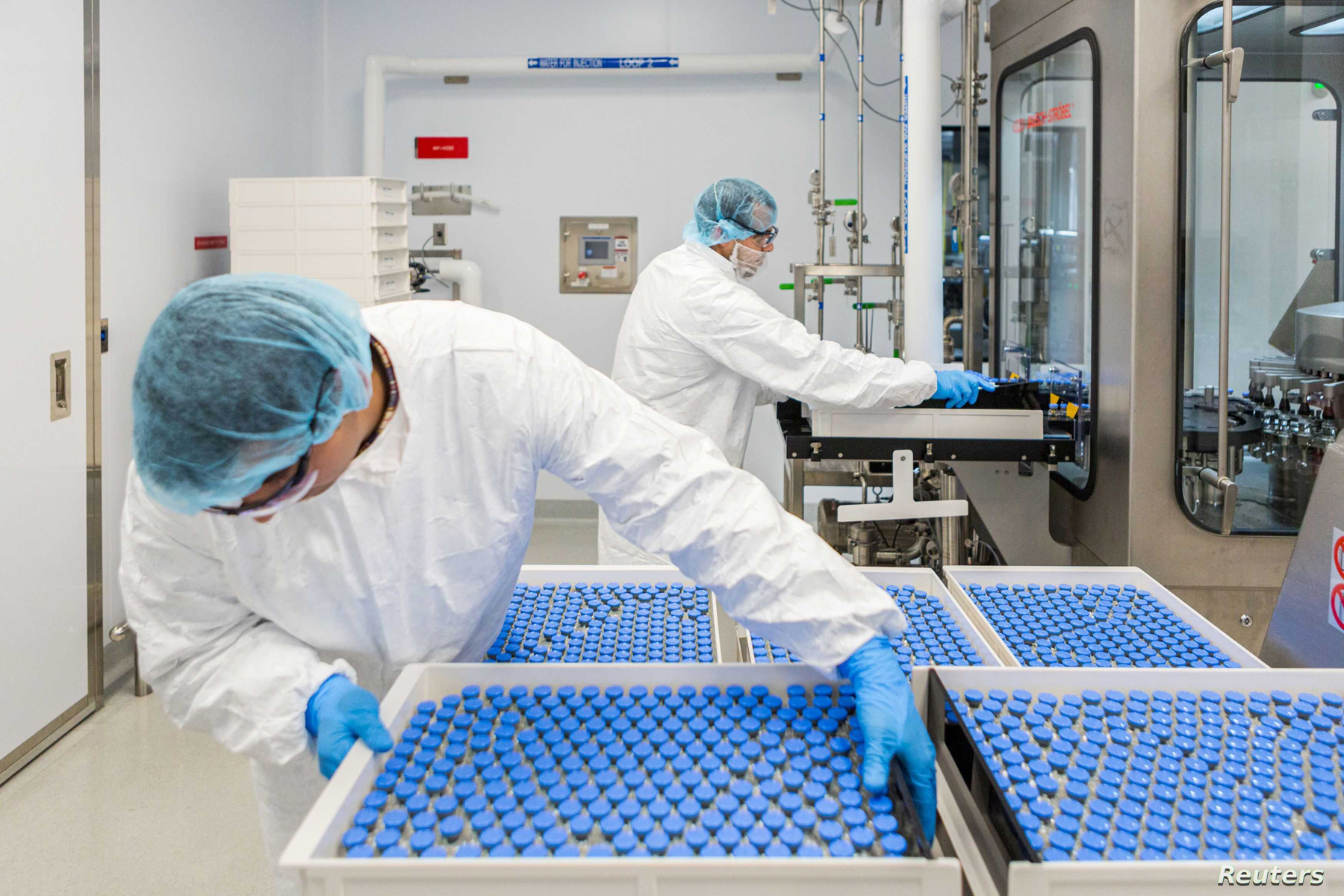 Lab technicians load filled vials of investigational coronavirus disease (COVID-19) treatment drug remdesivir at a Gilead Sciences facility in La Verne, California, U.S. March 18, 2020.