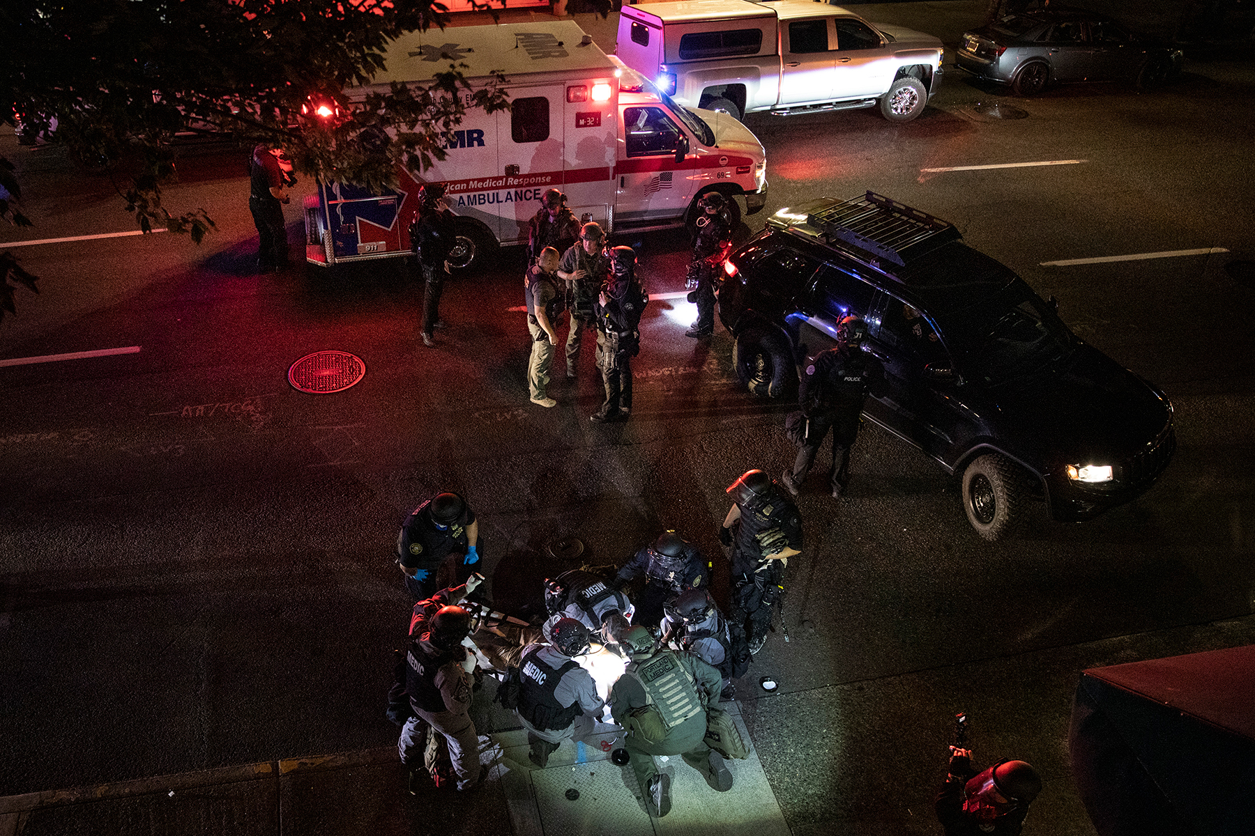 First responders treat a man who was fatally shot on Saturday, Aug. 29, 2020, in Portland, Ore