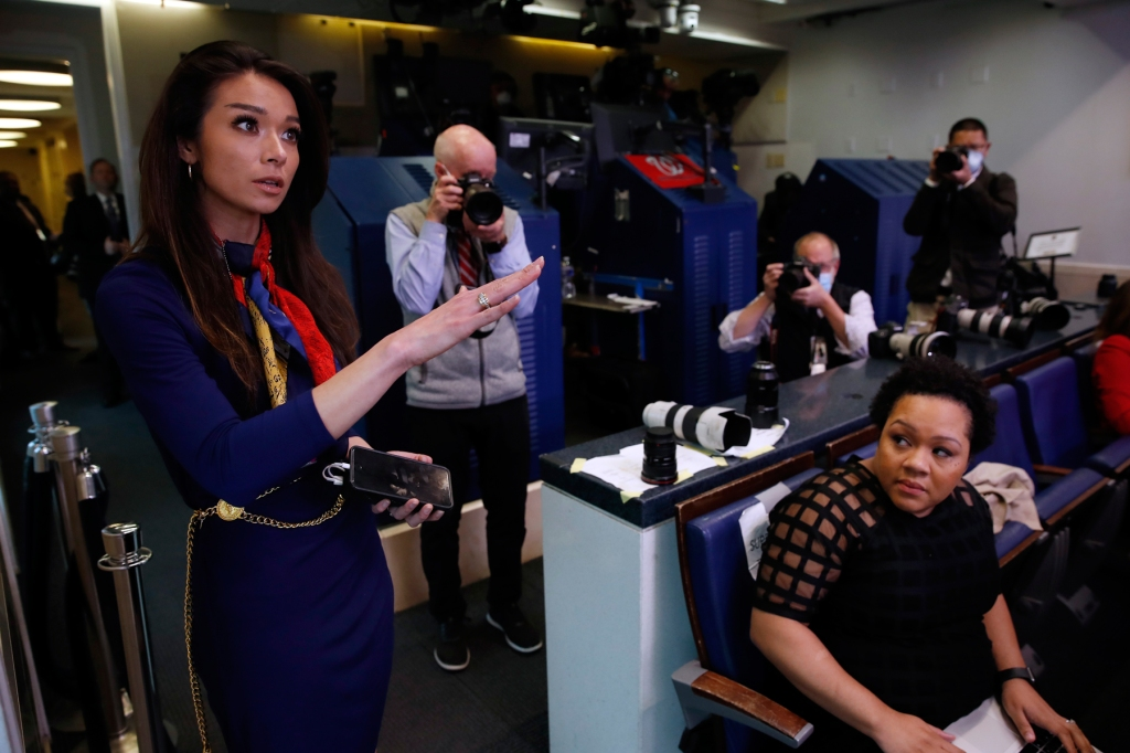 PBS reporter Yamiche Alcindor, seated, watches as One America News (OAN) White House Correspondent Chanel Rion asks a question of President Donald Trump during a briefing about the coronavirus in the James Brady Press Briefing Room of the White House, Monday, April 20, 2020, in Washington. (AP Photo/Alex Brandon)