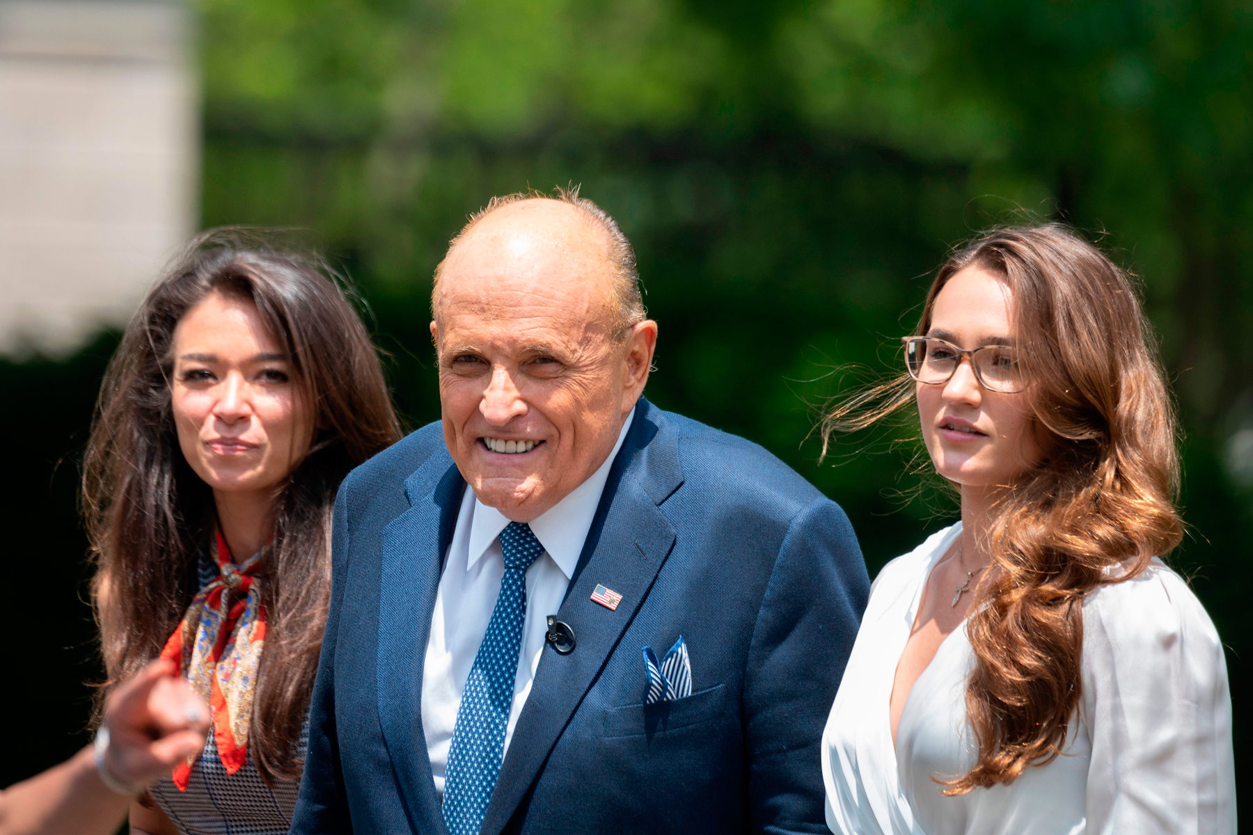 Rudy Giuliani (C), attorney for US President Donald Trump, walks with his personal Communications Director Christianne Allen (R) and One America News Network's Chanel Rion, after speaking at the White House in Washington, DC, on July 1, 2020. (Photo by JIM WATSON / AFP) (Photo by JIM WATSON/AFP via Getty Images)