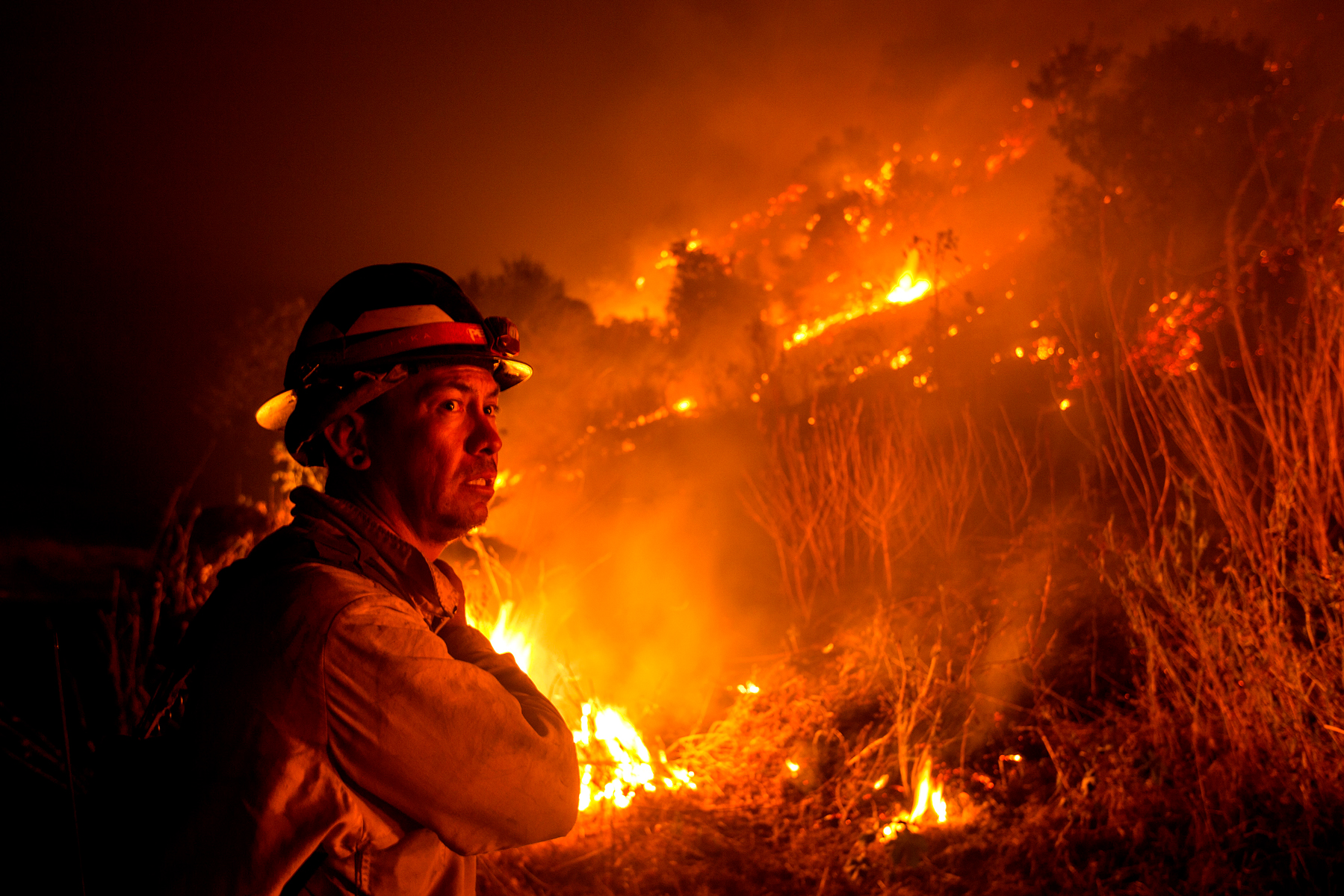 """A firefighter watches the Bobcat Fire burning on hillsides near Monrovia Canyon Park in Monrovia, California on September 15, 2020. - A major fire that has been raging outside Los Angeles for more than a week threatened to engulf a historic observatory and billion-dollar broadcast towers on September 15 as firefighters struggled to contain the flames. The so-called Bobcat Fire was within 500 feet (150 meters) from the 116-year-old Mt. Wilson Observatory, the US Forest Service said in a tweet, while fire officials said crews were in place """"ready to receive the fire."""" (Photo by RINGO CHIU / AFP) (Photo by RINGO CHIU/AFP via Getty Images)"""