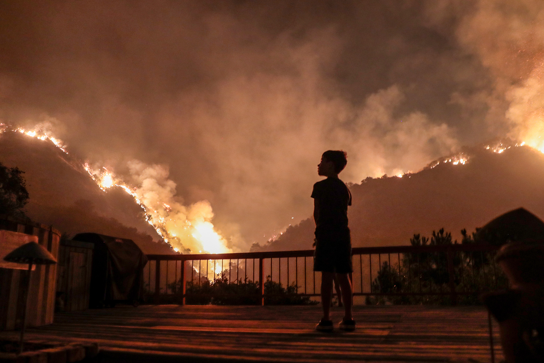 Monrovia, CA, September 15, 2020 - Castle Snider, 8, looks on as flames engulf the hillsides behind his backyard as the Bobcat Fire burns near homes on Oakglade Dr.  (Robert Gauthier/ Los Angeles Times via Getty Images)
