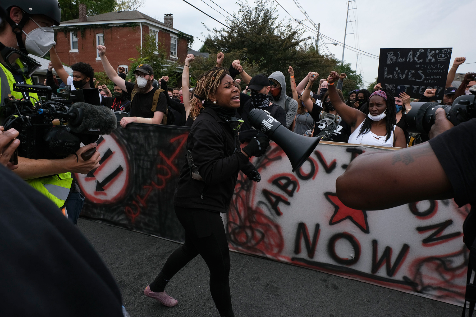 "A protestor calls for the crowd to ""Say Her Name Breonna Taylor"" while marching in downtown Louisville, Kentucky, on September 23, 2020, after a judge announced the charges brought by a grand jury against Detective Brett Hankison, one of three police officers involved in the fatal shooting of Breonna Taylor in March. - Hankison was charged today, September 23, with three counts of ""wanton endangerment"" in connection with the shooting of Taylor, a 26-year-old black woman whose name has become a rallying cry for the Black Lives Matter movement. (Photo by Jeff Dean / AFP) (Photo by JEFF DEAN/AFP via Getty Images)"