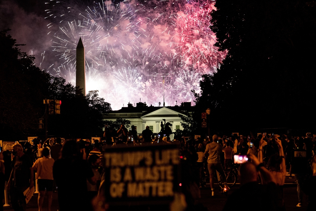 Protesters watch a fireworks display above the White House after President Donald Trump accepted the Republican presidential nomination during the final night of the Republican National Convention, in Washington, on Thursday, Aug. 27, 2020. (Erin Schaff/The New York Times)