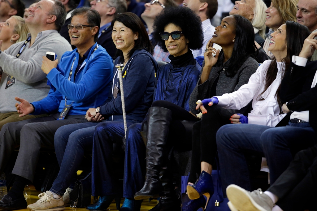 Singer Prince, center, smiles as he watches an NBA basketball game between the Golden State Warriors and the Oklahoma City Thunder Thursday, March 3, 2016, in Oakland, Calif. (AP Photo/Marcio Jose Sanchez)