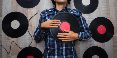 top view man (music lover) with headphones lie on the floor and listen music among retro vinyl records
