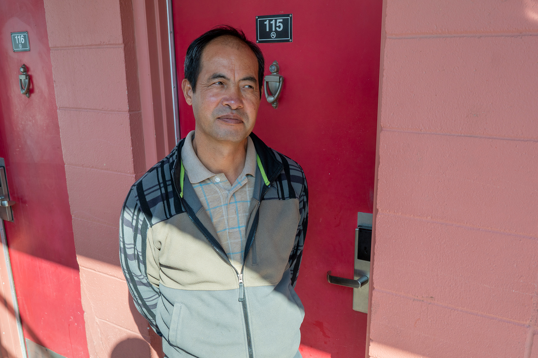 "Qinliang Wang in front of his room at a motel in Farmington, where he came to do what he thought was legal ""flower trimming"" after being out of the workforce since March. Two days later, he was arrested in the room while pruning marijuana."
