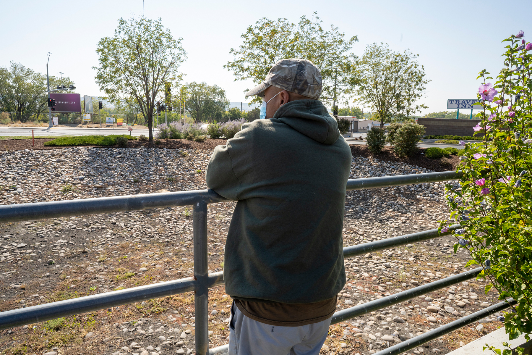 Mr. Zhang, who poured in his life savings into what he thought was a legal cannabis farm, gazes over the fence at a Walmart parking lot in Farmington.