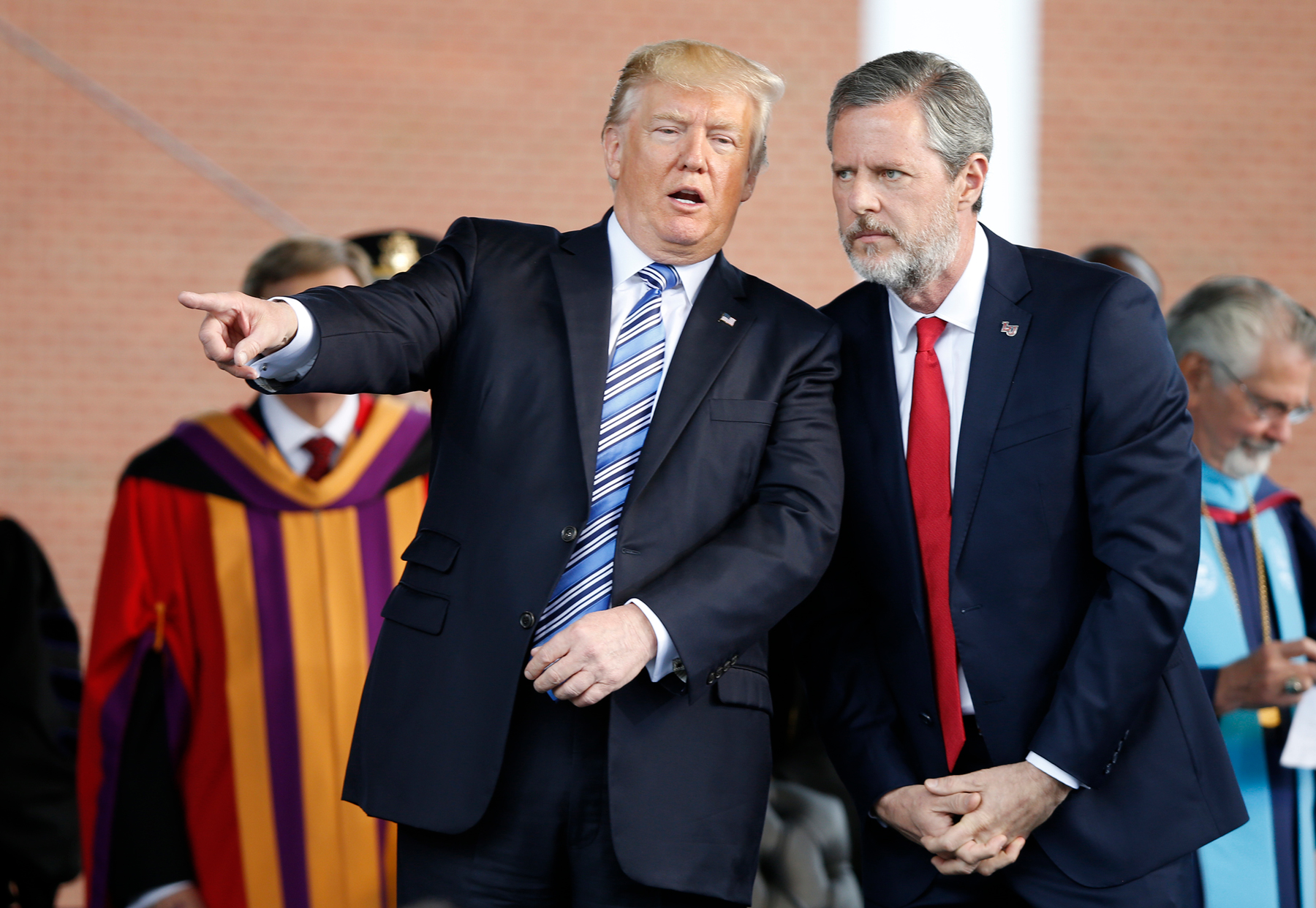 "FILE - In this May 13, 2017 file photo, President Donald Trump gestures as he stands with Liberty University president, Jerry Falwell Jr., right, during commencement ceremonies at the school in Lynchburg, Va. Falwell Jr., said in an interview that he and President Donald Trump are in regular communication but described himself as ""not a spiritual adviser, not a counselor. I'm just his friend."" (AP Photo/Steve Helber)"