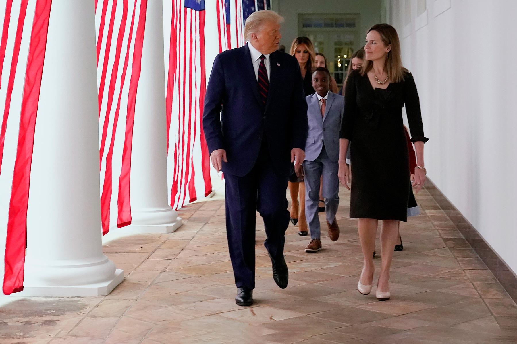 President Donald Trump walks along the Colonnade with Judge Amy Coney Barrett after a news conference to announce Barrett as his nominee to the Supreme Court, in the Rose Garden at the White House, Saturday, Sept. 26, 2020, in Washington. (AP Photo/Alex Brandon)