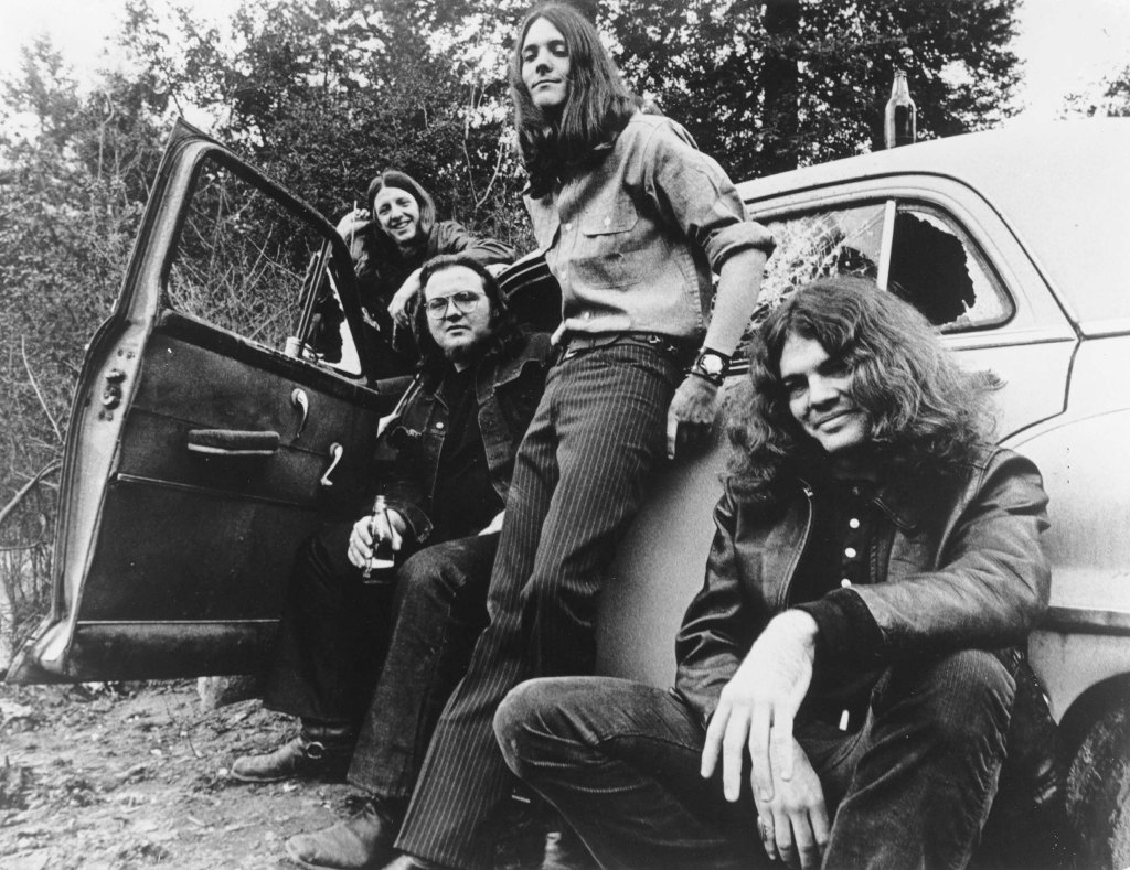 "CIRCA 1970: (L-R) Pat Simmons, John Hartman, Dave Shogren and Tom Johnston of the rock and roll band ""The Doobie Brothers"" pose for a portrait with a car in circa 1970. (Photo by Michael Ochs Archives/Getty Images)"
