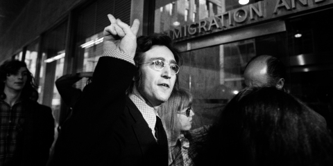Musician John Lennon flashes a peace sign as he and Yoko Ono appear at the New York office of Immigration and Naturalization in May of 1972 to fight deportation proceedings.